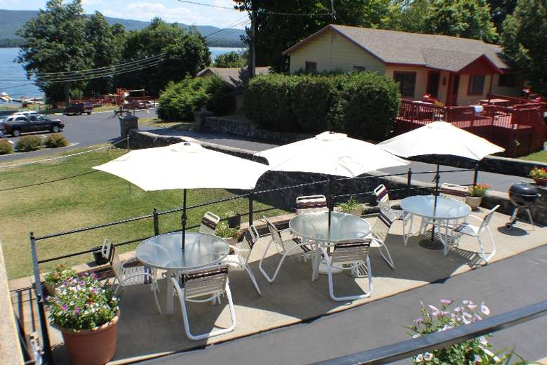 three outdoor patio tables with chairs and umbrellas. There is a grassy lawn with volleyball / badminton net to the right.