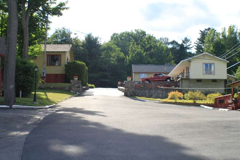 a driveway leading up to motel rooms with neat landscaping on each side