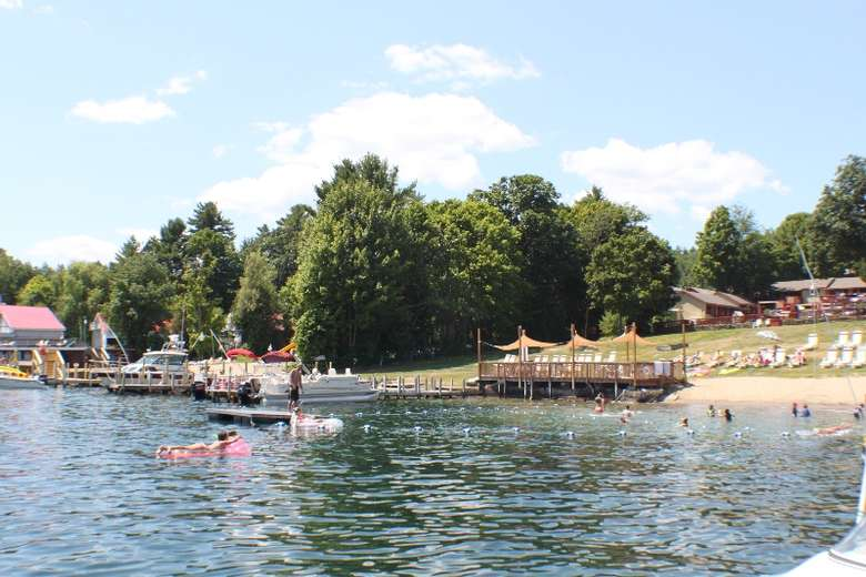 people swimming in the lake with the docks to the left and the beach in the background