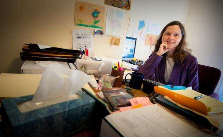Woman in front of cluttered desk