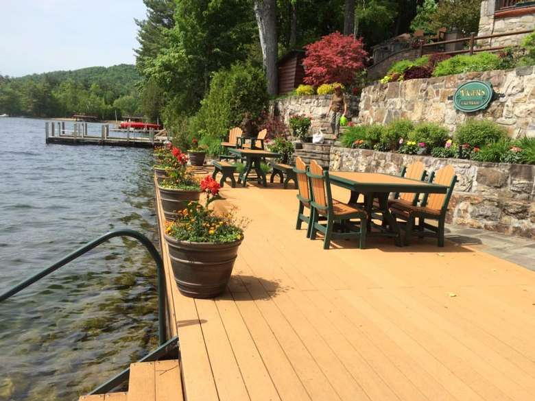 waterfront deck with bushes and flowers along a stone wall