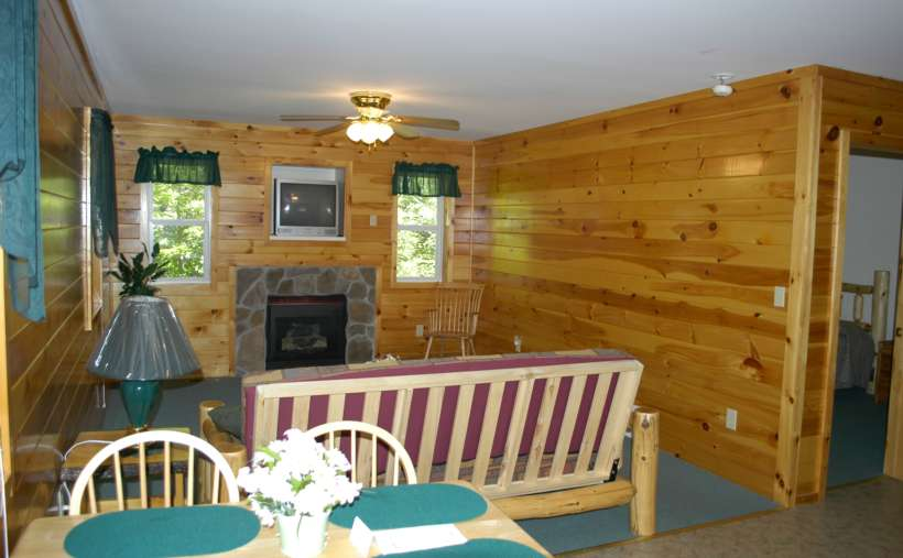 inside a cottage with a futon, tables and chairs, fireplace