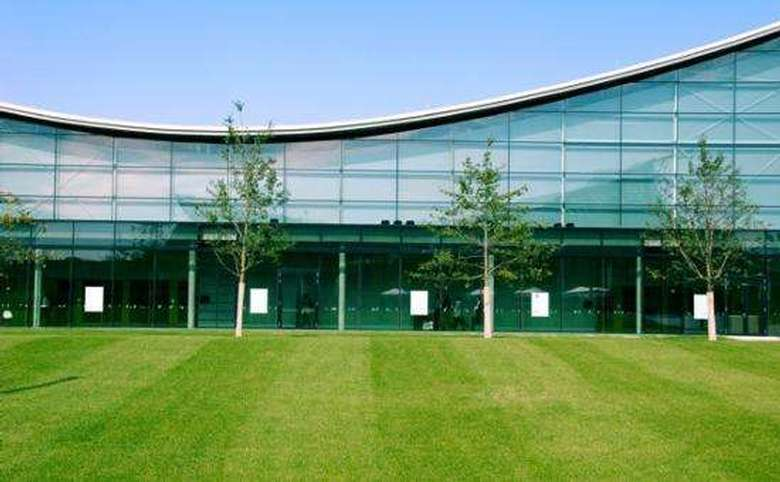Large building with glass walls and trees out front