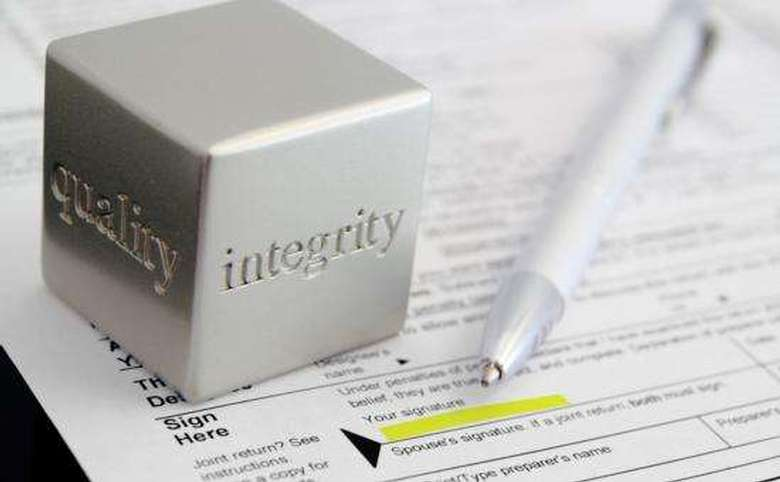 Silver block that says quality and integrity on top of a contract