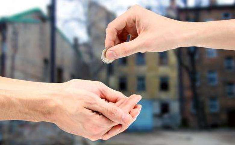 Hand giving a quarter to outstretched hands