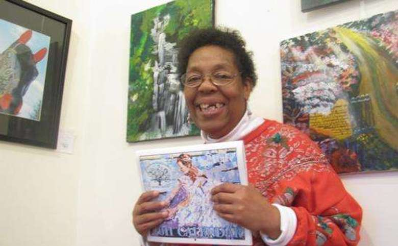 woman holding a calendar with paintings in the background