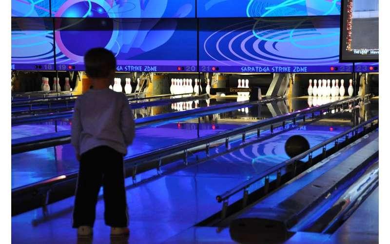 a kid watching their bowling ball roll