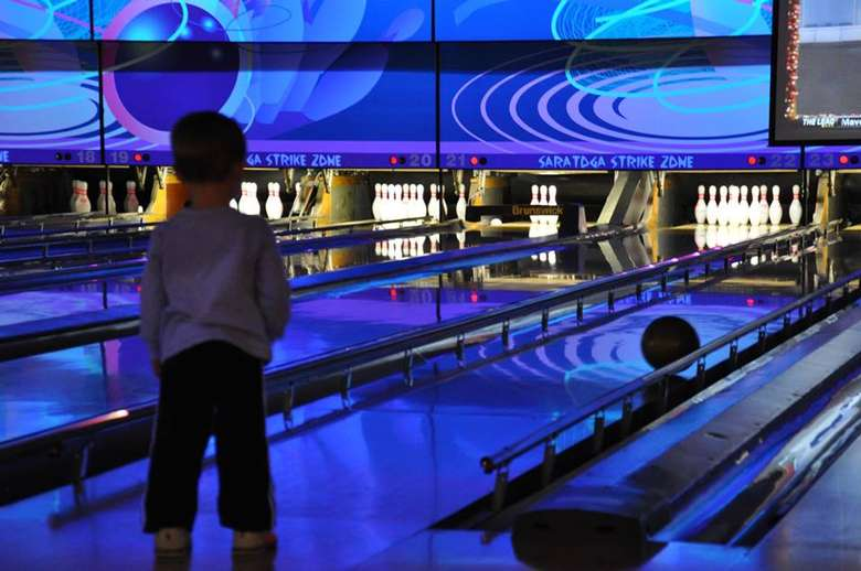 a kid watching their bowling ball roll