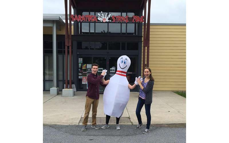 a man and woman standing with someone dressed as a bowling pin