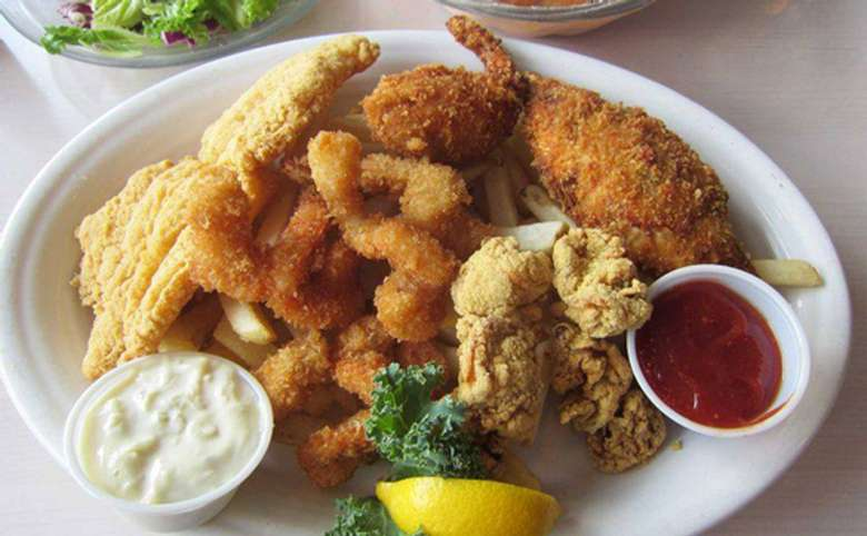 A fried fish platter with shrimp, fish filet and clams, as well as french fries, ketchup, tartar sauce, and lemon.