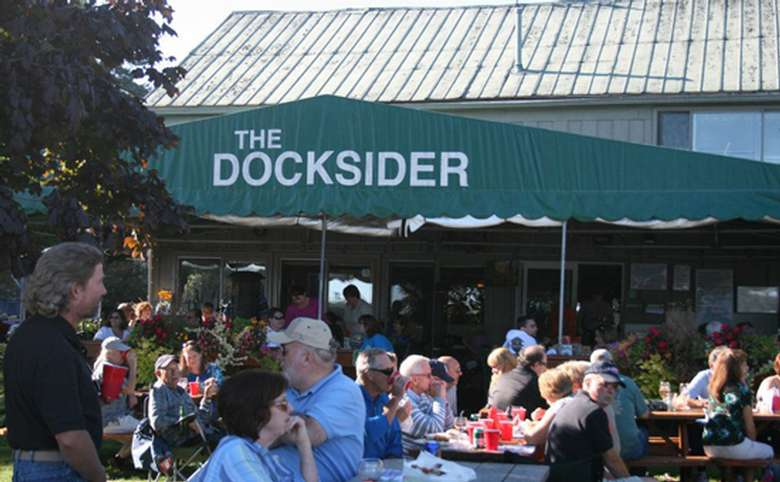 An outdoor picnic dining area at The Docksider, showing several people dining at picnic tables and drinking from red plastic cups