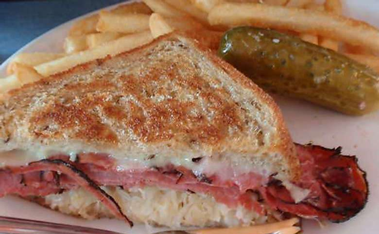 A grilled Reuben sandwich made with corned beef, sauerkraut and cheese, plus french fries and a pickle.