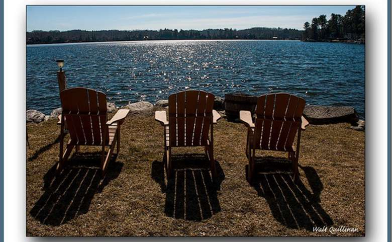 Three Adirondack chairs facing the lake. The sun is reflected off the water, creating a sparkling effect. There are trees and forests in the background.