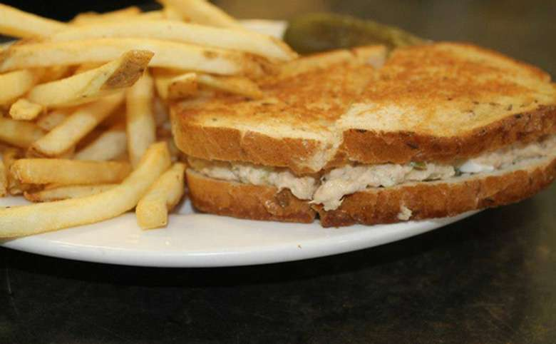 A grilled tuna salad sandwich on a white plate with french fries and a pickle