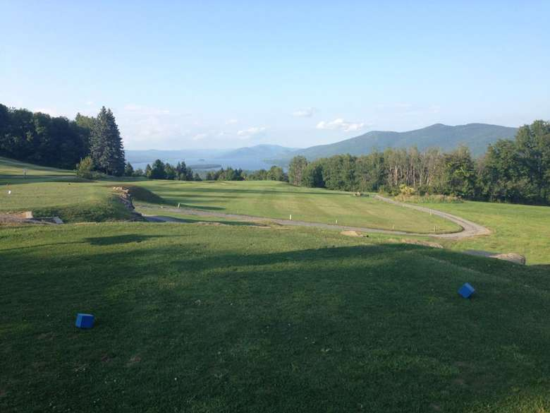 View of golf course with Lake George and mountains in the background