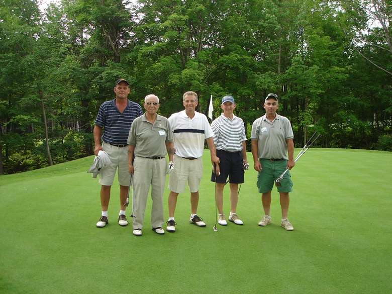 Five men holding golf clubs on the course