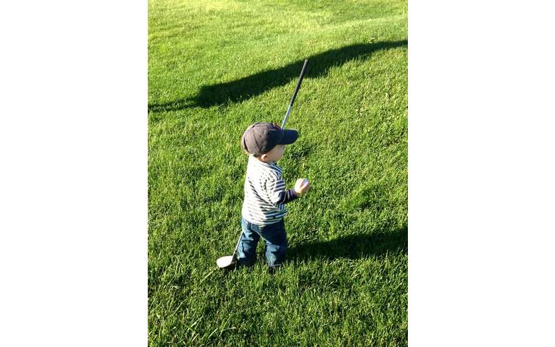 A little boy with a golf club and ball standing in the grass