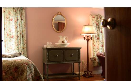 part of the bedroom with a  dresser, mirror, lamp