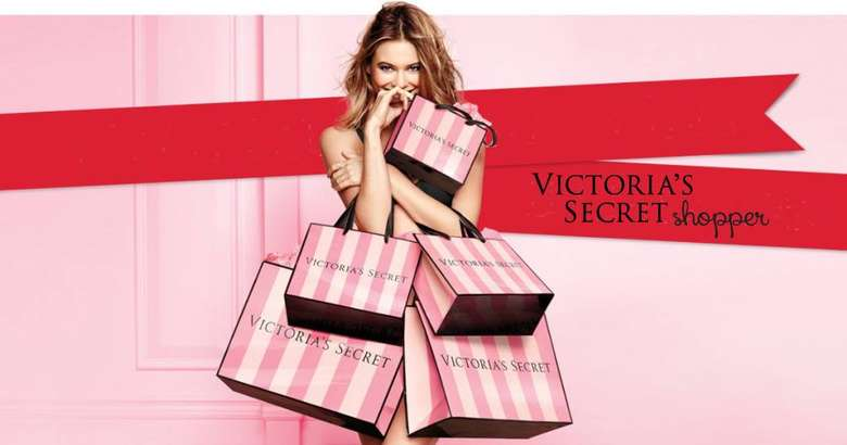 Victoria's Secret ad with woman holding a bunch of bags
