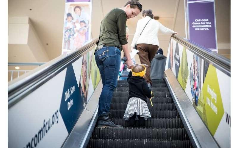 a woman helping a toddler up an escalator