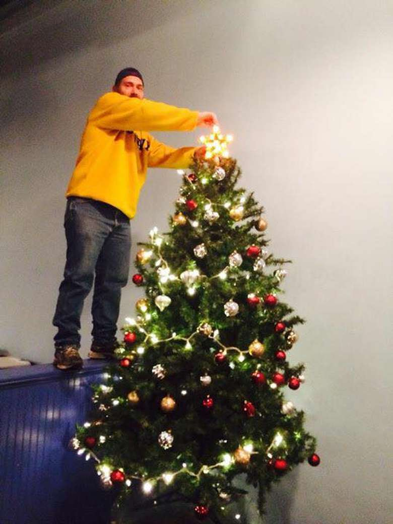 Man decorating a  Christmas tree