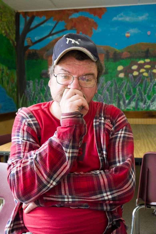 Man looking at camera, sitting