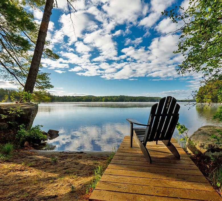 adirondack chair on a wooden dock by a lake