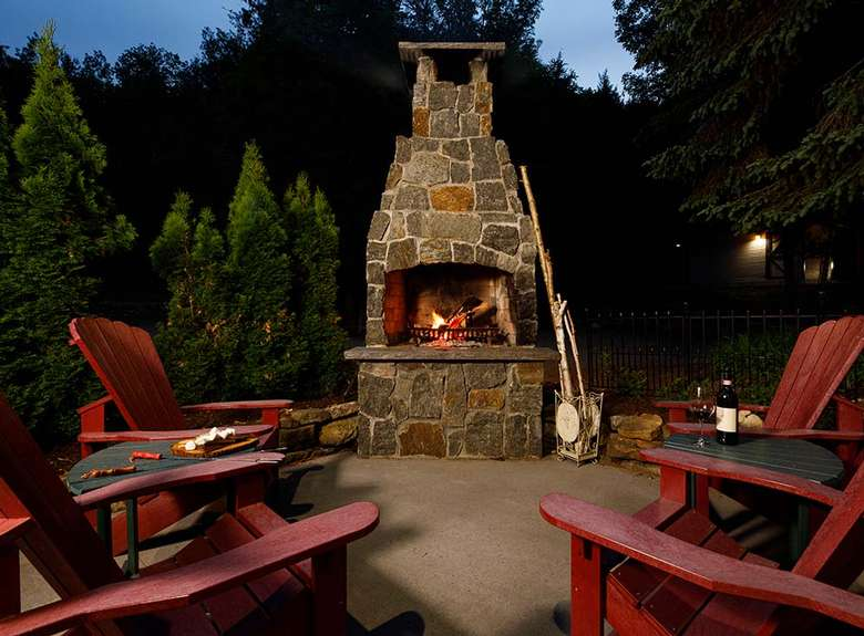 red adirondack chairs by an outdoor stone fireplace