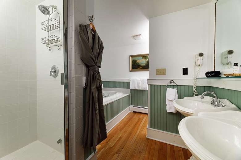bathroom with sinks, bathrobe hanging from a hook, a shower, and a tub