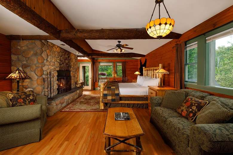 large rustic hotel room with stone fireplace, bed, couches, and table