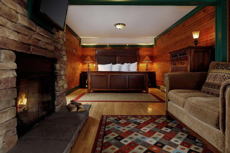 rustic hotel room with fireplace, large bed, and couch