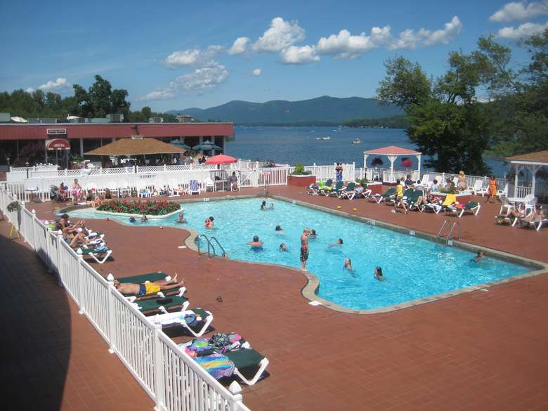 people swimming in the pool at the georgian overlooking lake george