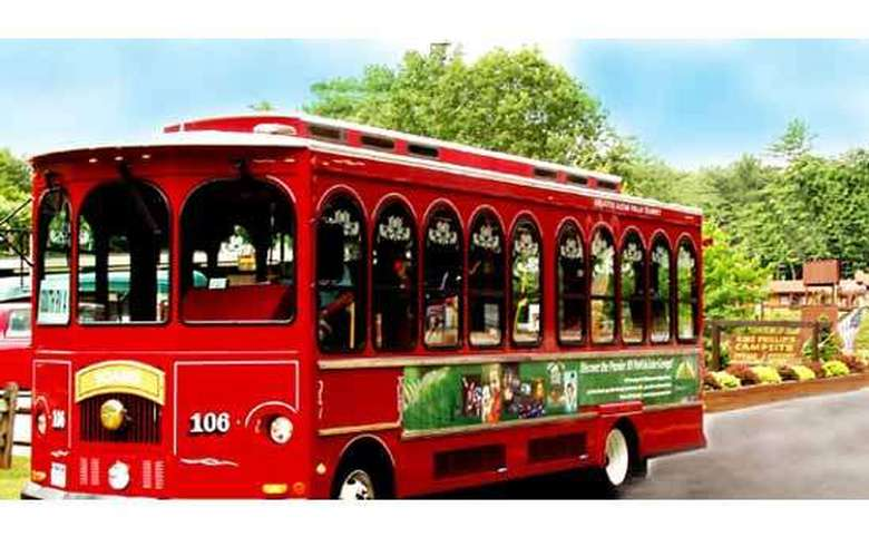 a red trolley driving down the road