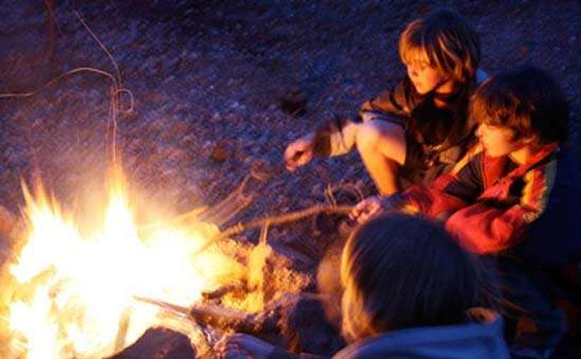 some kids sitting by a fire roasting marshmallows
