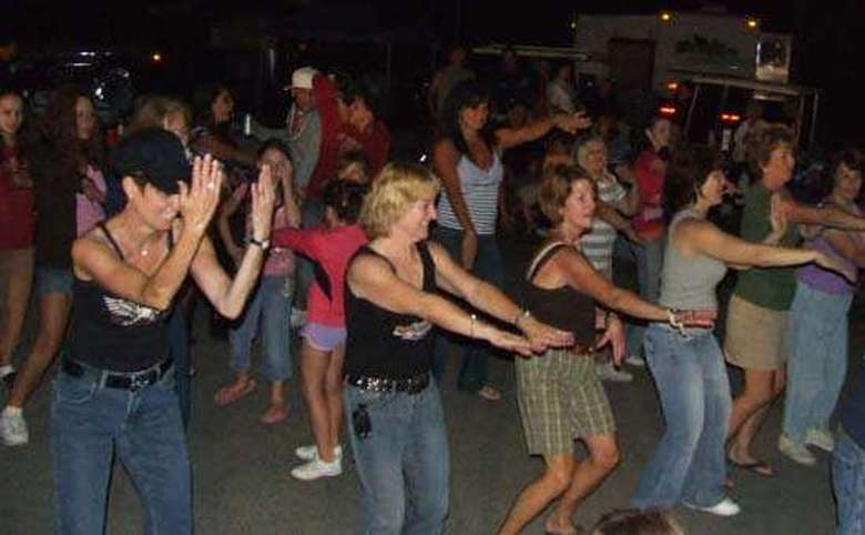 group of people dancing together at a party outside