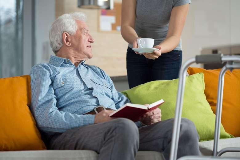 a person handing an elderly man a coffee mug