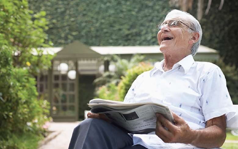 an elderly man in a chair laughing while holding a newspaper in his lap