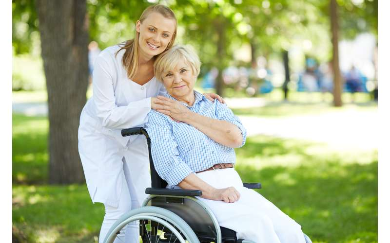 a woman in an official white outfit hugging a woman in a wheelchair