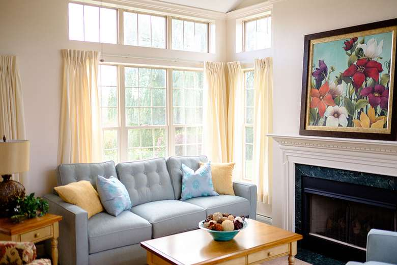 a lounge area with a painting above a fireplace and a blue couch with a table in front of it