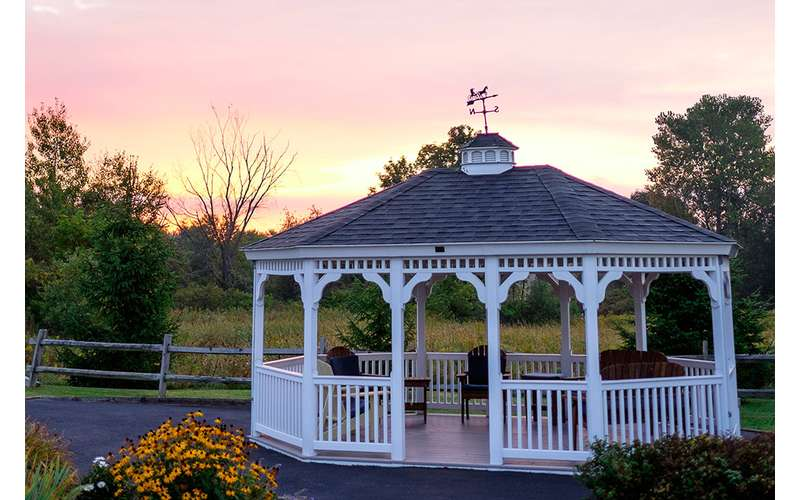 a large white gazebo near panoramic surroundings in the evening