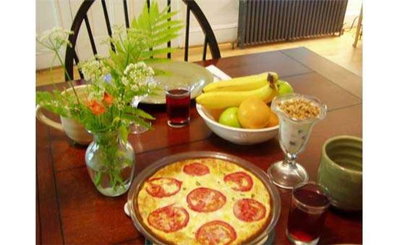 table with a fresh egg casserole and a bowl of fruit on it