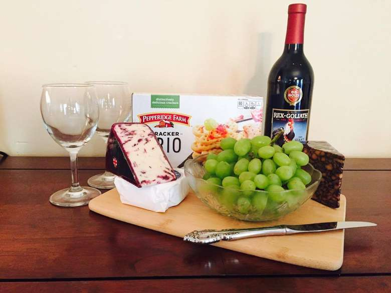 cutting board with multiple types of cheese, crackers, and green grapes with a bottle of wine and two glasses next to it