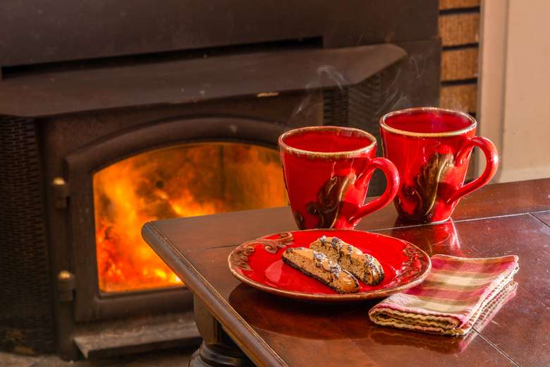 two mugs of coffee and biscotti sitting on table beside a fireplace
