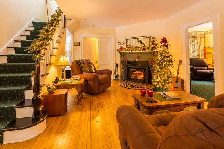 living room with brown couch and recliner, coffee table and crackling fireplace and staircase