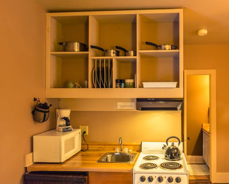 kitchenette unit with small refrigerator, stove, microwave, coffee pot, sink, and dishes