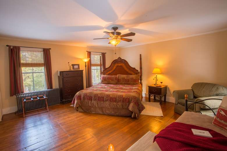 large bedroom with hardwood floors, king bed, dresser and ceiling fan