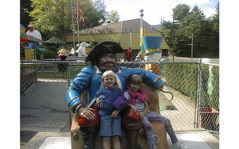 A young boy and a young girl sitting on a bench with a pirate statue