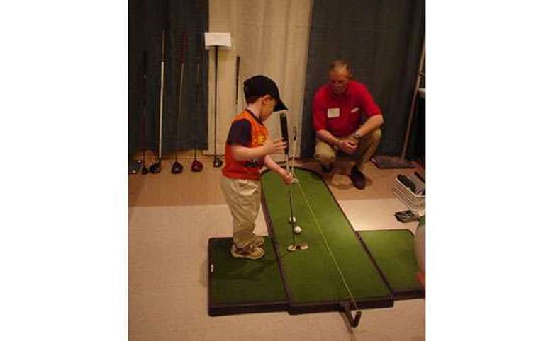 young boy using an adult sized putter to play with an indoor putting green
