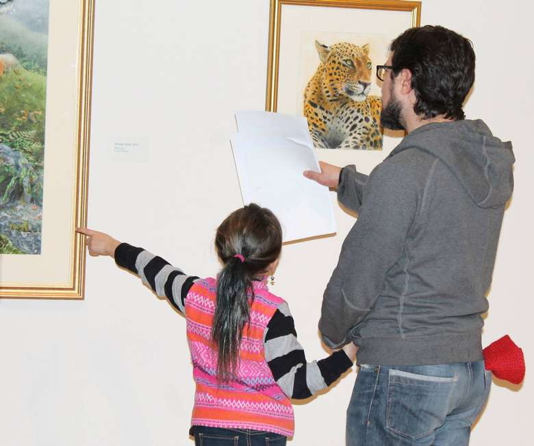 a man holding a piece of paper near artworks, a girl is near him