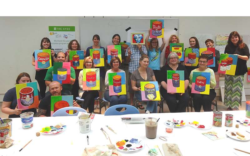 a group of paint and sip participants with their finished works